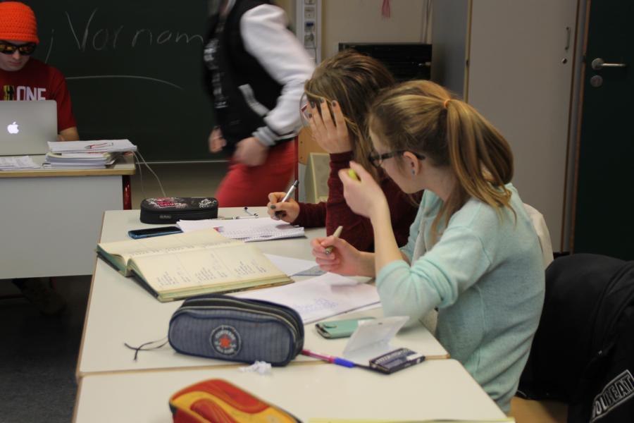 Schülerinnen beim Entziffern von schwer zu lesenden Handschriften