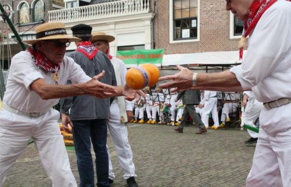 Männer in traditioneller Kleidung werfen Käse